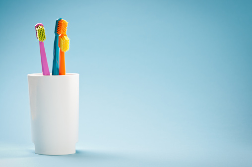 Dental Health「Three colourful soft toothbrushes in white mug on blue background」:スマホ壁紙(7)