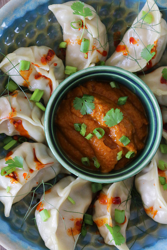 Chinese Dumpling「Image of steamed Momos (South Asian dumplings), white flour and water dough filled with chicken and mixed vegetables, drizzled with chilli oil, on plate surrounding ramekin of orange spicy dipping sauce, elevated view」:スマホ壁紙(10)