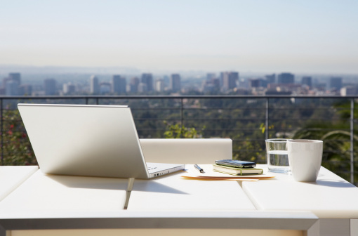 City「Laptop and paperwork on balcony table」:スマホ壁紙(6)