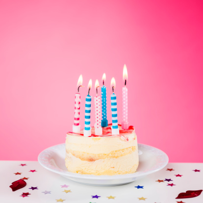 Anniversary「Birthday cake with candles standing on the table, pink background」:スマホ壁紙(16)