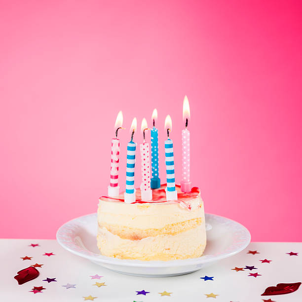 Birthday cake with candles standing on the table, pink background:スマホ壁紙(壁紙.com)