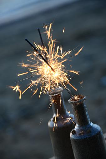 花火「Lit sparklers in glass bottles on beach」:スマホ壁紙(6)