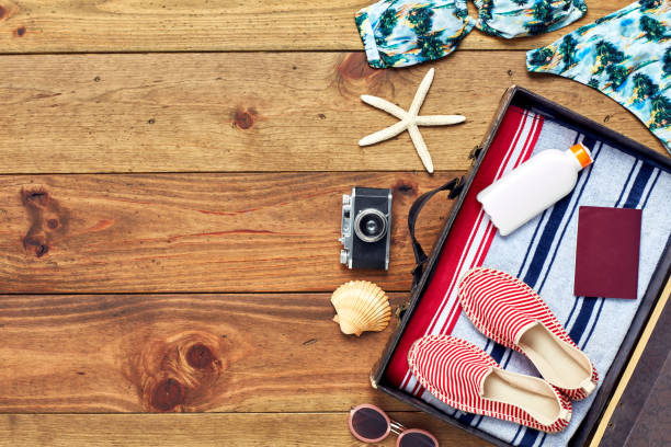 Open suitcase with summer vacation equipment flat lay on wood:スマホ壁紙(壁紙.com)