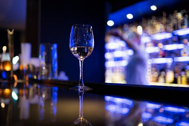 Glass of white wine on bar counter:スマホ壁紙(壁紙.com)