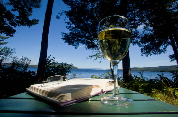 A glass of white wine, a book and eyeglasses on a green painted table overlooking Moosehead Lake in Maine, USA:スマホ壁紙(壁紙.com)