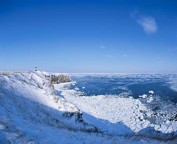 A Lighthouse on a Snowy Cliff Overlooking Drift Ice and the Ocean. Abashiri, Hokkaido, Japan:スマホ壁紙(壁紙.com)