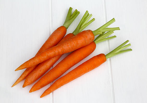Pile of fresh carrots with tops removed, on white:スマホ壁紙(壁紙.com)