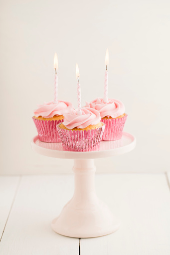 カップケーキ「Three pink cup cakes with lighted birthday candles on a cakestand」:スマホ壁紙(5)