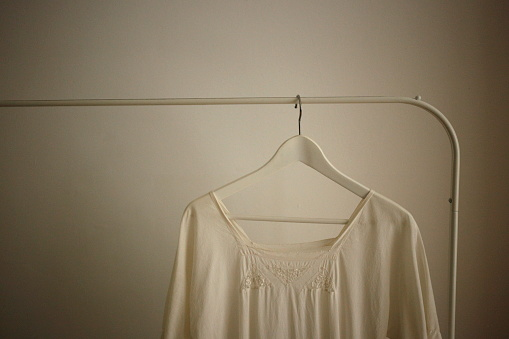 Girly「White dress hanging on white stand against a white wall background」:スマホ壁紙(15)