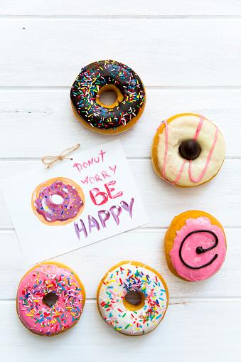 幸福「Selection of donuts with multi-colored icing with note」:スマホ壁紙(12)