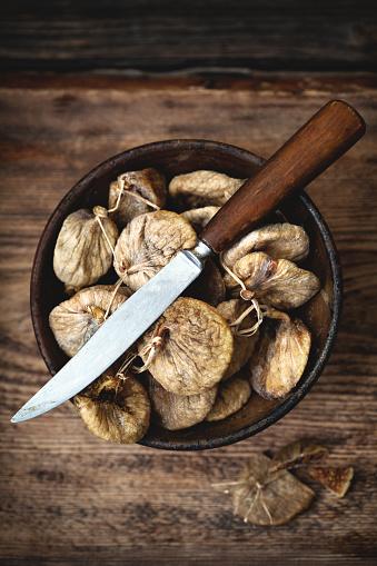 イチジク「木製テーブルの上のナイフで茶色ボウルでイチジクを乾燥させた。」:スマホ壁紙(7)