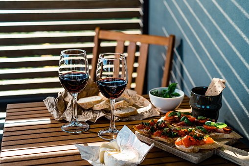 French Food「Two glasses of red wine with antipasto snacks on a table outdoors」:スマホ壁紙(5)