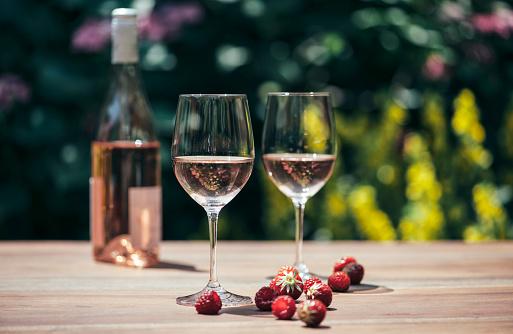 Wine Bottle「Two glasses of rose wine, wine bottle, strawberries and raspberries on wooden table」:スマホ壁紙(10)