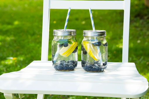 Infused Water「Two glasses of infused water with lemon slices, blueberries and mint on garden chair」:スマホ壁紙(10)