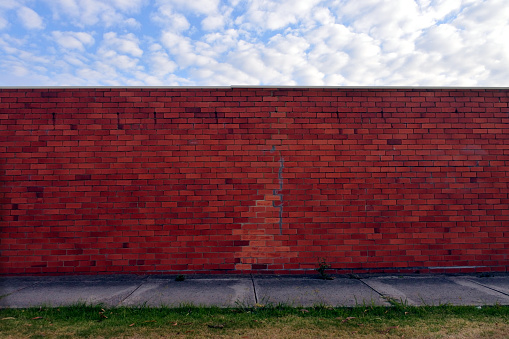 Brick Wall「Brick wall under a cloudy sky in urban city sidewalk」:スマホ壁紙(3)