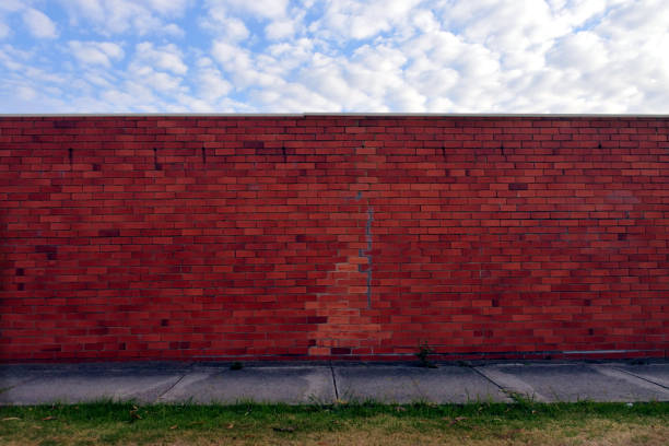 Brick wall under a cloudy sky in urban city sidewalk:スマホ壁紙(壁紙.com)