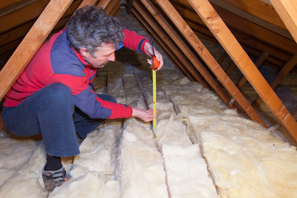 Insulation「A man measuring the depth of insulation in a house loft or roof space. Insulating your loft can save a significant amount of household heat loss and therefore help save energy and help combat climate change」:写真・画像(13)[壁紙.com]