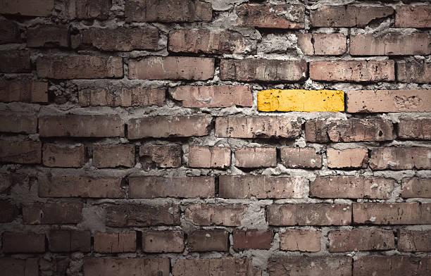 Brown brick wall with one gold brick:スマホ壁紙(壁紙.com)