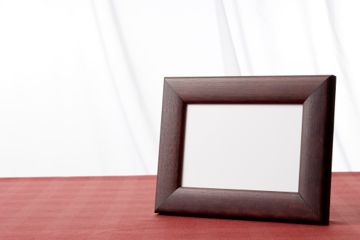 Standing「Blank wooden picture frame on the table with copy space」:スマホ壁紙(0)