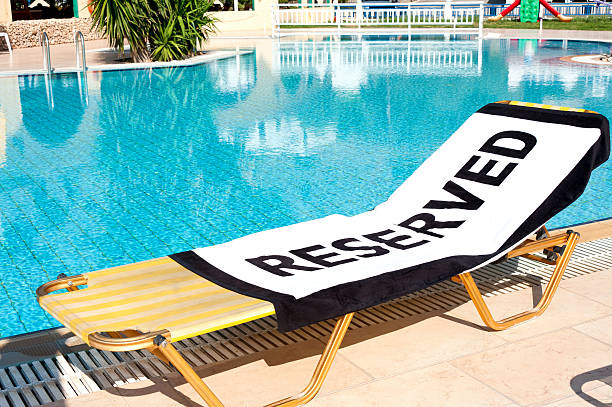 Lounge chair next to pool with 'Reserved' towel:スマホ壁紙(壁紙.com)