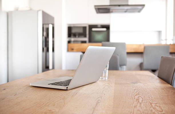 Laptop on wooden table in an open plan kitchen:スマホ壁紙(壁紙.com)