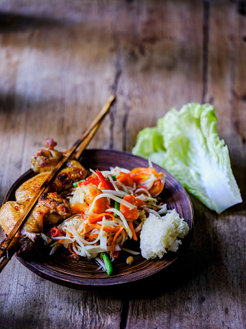 PGA Event「Som Tam Tai, a popular and favourite Thai food dish made of young sliced papaya, chili, tomatoes, palm sugar and dried shrimp, served with grilled chicken wings and sticky rice on an old wooden table.」:スマホ壁紙(16)