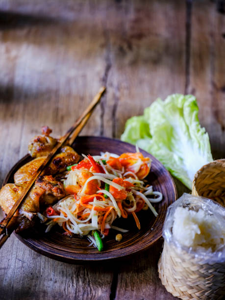 Som Tam Tai, a popular and favourite Thai food dish made of young sliced papaya, chili, tomatoes, palm sugar and dried shrimp, served with grilled chicken wings and sticky rice on an old wooden table.:スマホ壁紙(壁紙.com)
