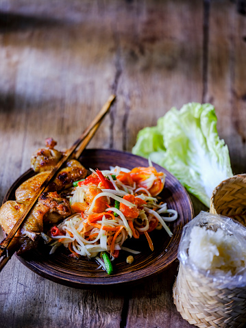 PGA Event「Som Tam Tai, a popular and favourite Thai food dish made of young sliced papaya, chili, tomatoes, palm sugar and dried shrimp, served with grilled chicken wings and sticky rice on an old wooden table.」:スマホ壁紙(12)
