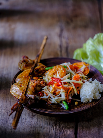PGA Event「Som Tam Tai, a popular and favourite Thai food dish made of young sliced papaya, chili, tomatoes, palm sugar and dried shrimp, served with grilled chicken wings and sticky rice on an old wooden table.」:スマホ壁紙(14)