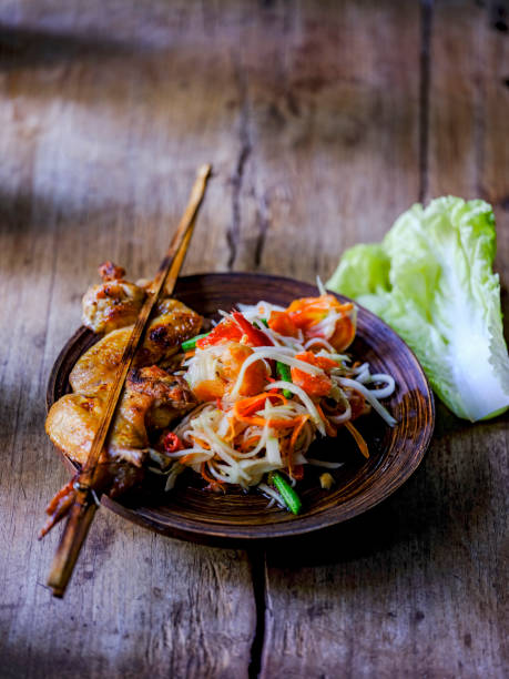 Som Tam Tai, a popular and favourite Thai food dish made of young sliced papaya, chili, tomatoes, palm sugar and dried shrimp, served with grilled chicken wings on an old wooden table.:スマホ壁紙(壁紙.com)
