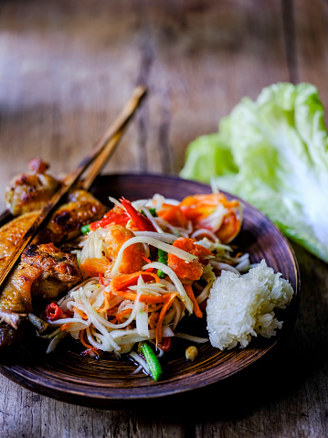 PGA Event「Som Tam Tai, a popular and favourite Thai food dish made of young sliced papaya, chili, tomatoes, palm sugar and dried shrimp, served with grilled chicken wings and sticky rice on an old wooden table.」:スマホ壁紙(17)