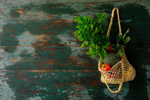 Farm「Many colorful contrast color salad vegetables in a reusable string hemp bag hanging from an old weathered abstract color contrasting turquoise colored background wall.」:スマホ壁紙(1)