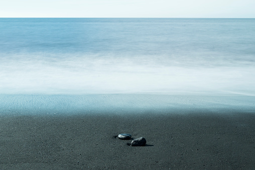 水色「Island, two pebbles lying on dark sandy beach at waterfront」:スマホ壁紙(12)