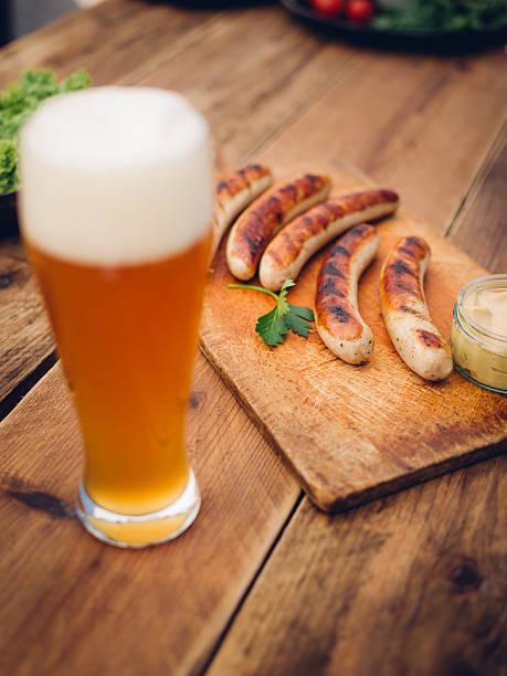 Cold beer with grilled bratwurst sausages on a wooden table:スマホ壁紙(壁紙.com)