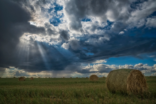 cloud「Sunlight breaks through the storm clouds over a field of hay bales」:スマホ壁紙(14)