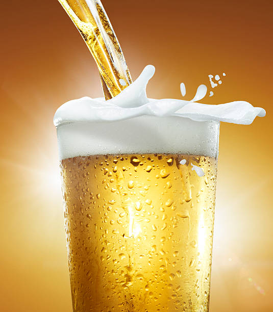 Pouring a glass of beer with foam overflowing.:スマホ壁紙(壁紙.com)