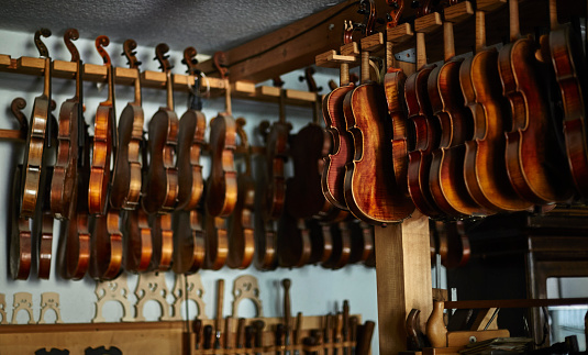 Violin「Violins hanging in a row in a luthier's workshop」:スマホ壁紙(17)