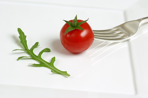 Arugula「Cherry tomato pierced with fork beside rocket leaf on plate, close-up」:スマホ壁紙(9)