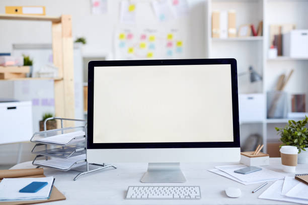 Blank screen of desktop computer on modern table with papers, sketchpads and file container in office:スマホ壁紙(壁紙.com)