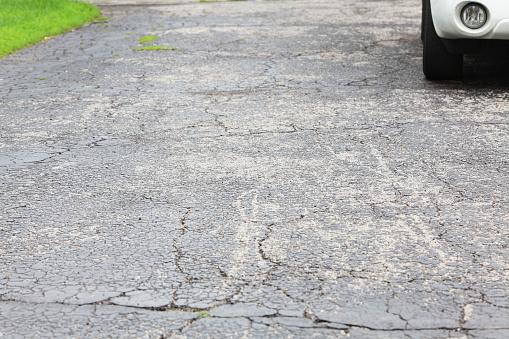 Dirty「Cracked asphalt driveway with car parked」:スマホ壁紙(12)