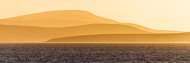 Sunrise over orange hills and blue ocean:スマホ壁紙(壁紙.com)