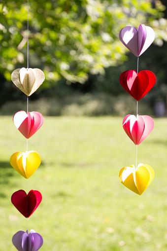 Heart「Heart-shaped garland made of paper hanging in garden」:スマホ壁紙(2)