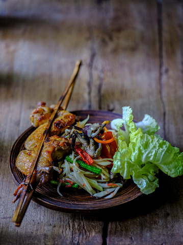PGA Event「Som Tam Boo, a popular and favourite Thai food dish made of young sliced papaya, chili, tomatoes, palm sugar and freshwater crab, served with grilled chicken wings on an old wooden table.」:スマホ壁紙(8)