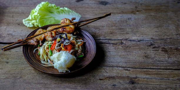 Som Tam Boo, a popular and favourite Thai food dish made of young sliced papaya, chili, tomatoes, palm sugar and freshwater crab, served with grilled chicken wings on an old wooden table.:スマホ壁紙(壁紙.com)