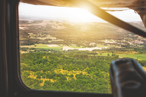 Passenger「Looking through small flying plane window at sunset in summer in countryside POV view」:スマホ壁紙(0)