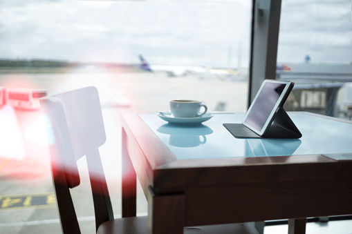 Convenience「Coffee cup and digital tablet on table at airport」:スマホ壁紙(15)