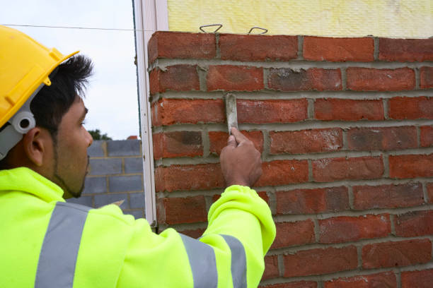 Bricklayer smoothing mortar on a newly erected brickwall House building site, England, UK:ニュース(壁紙.com)