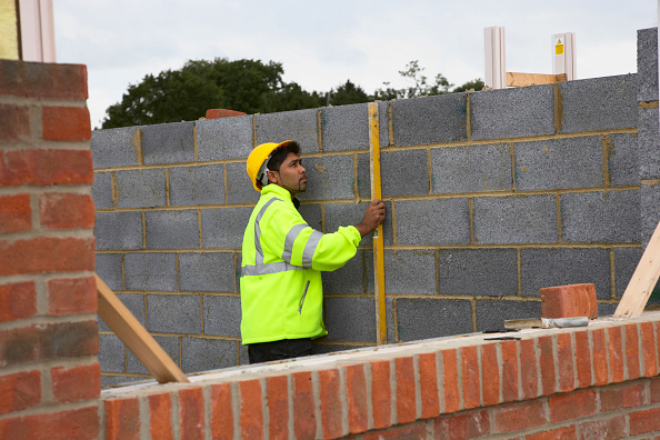 Measuring「Bricklayer checking levels on a breezeblock wall House building site, England, UK」:写真・画像(8)[壁紙.com]