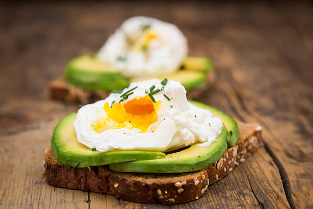 Wholemeal bread slices with sliced avocado and poached eggs on wood:スマホ壁紙(壁紙.com)