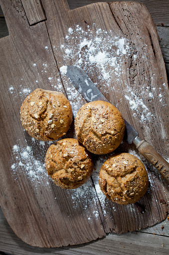 Bun - Bread「Wholemeal bread rolls, old bread knife and flour on wooden chopping board」:スマホ壁紙(6)